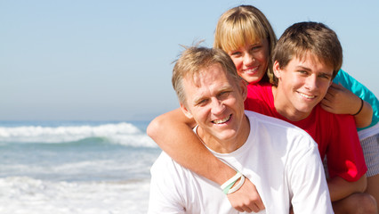 happy middle-aged father with teen kids on beach