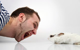 Young man and a rabbit on white background