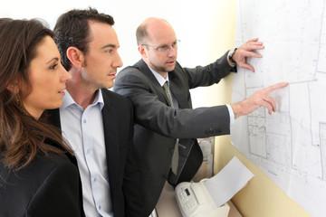 Couple et promoteur devant un plan d'architecte