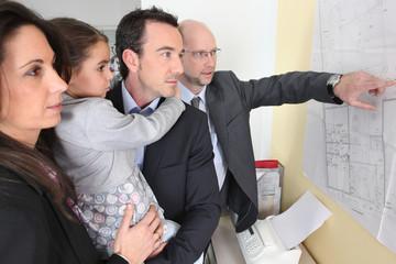 famille et promoteur devant un plan d'architecte