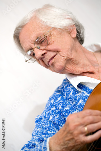 Elderly  woman playing guitar.