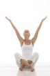 young woman dressed in white sitting cross-legged doing yoga