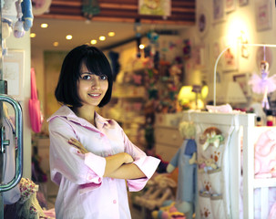 small business owner: proud woman opening her baby store