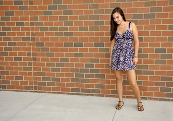 teen girl standing by a brick wall