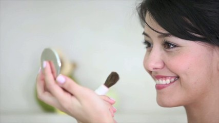 Beautiful woman putting blush on her chicks - make up concepts