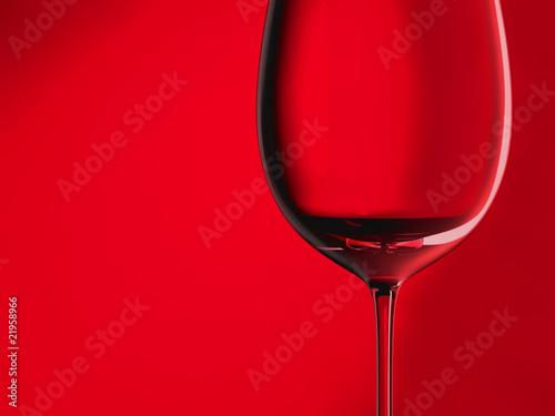 Leeres Rotweinglas vor rotem Hintergrund