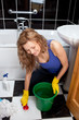 Smiling young woman cleaning bathroom's floor