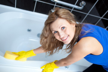 Smiling woman cleaning a bath