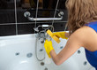 Woman cleaning with a sponge and detergent spray