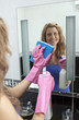 Smiling woman cleaning bathroom's mirror