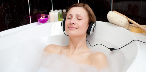 Relaxed woman listening music in a bubble bath