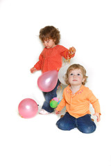 two toddler girls with colorful balloons