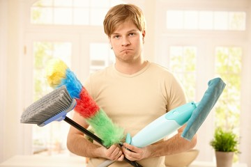 Upset guy with cleaning tools