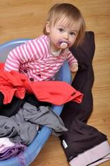 bébé avec tétine joue avec lessive