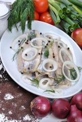 Matjesfilets auf einem Teller mit Zwiebelringen
