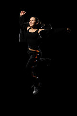 Female dancer jumping on black