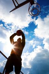 Basketballspieler im Gegenlicht beim werfen