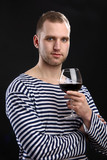 Young handsome man in sailor's jacket holding a glass of wine