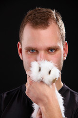 Young man and domestic rabbit on black background