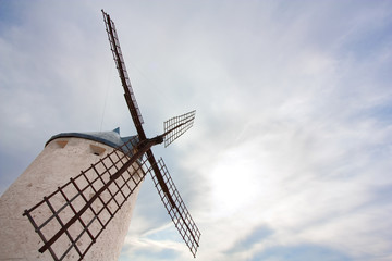 Windmill against cloudy sky