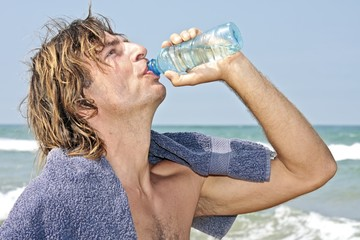 Young guy drinking fresh water after working out at the beach