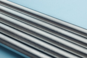 Rows of metal coil springs on blue with selective focus