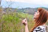 girl blowing on dandelion outdoors