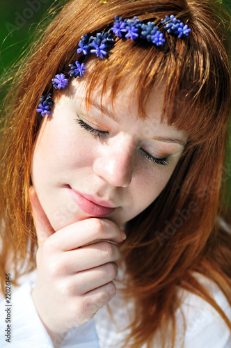 face of redheaded girl in spring forest