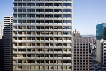 A repetitive building facade represents modern life