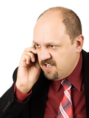 Spiteful businessman talking by mobile phone