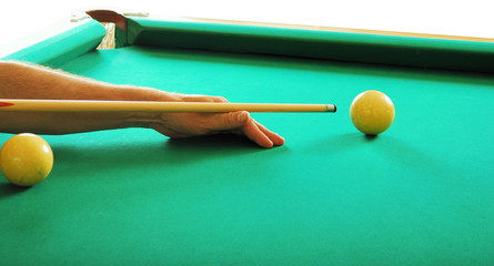 hand with a cue and billiards balls