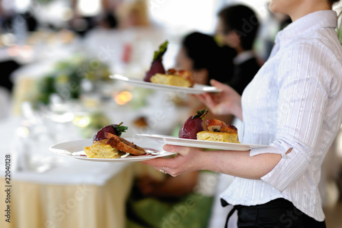Waitress is carrying three plates - 22040128