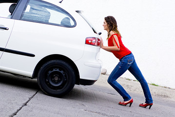 woman pushing car out of gasoline