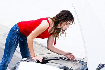 Female checking car motor failure