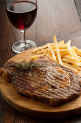 porterhouse with french fry and glass of red wine vertical