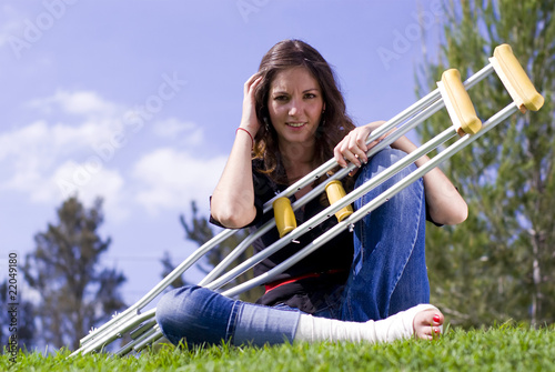 Woman seated with crutches outside