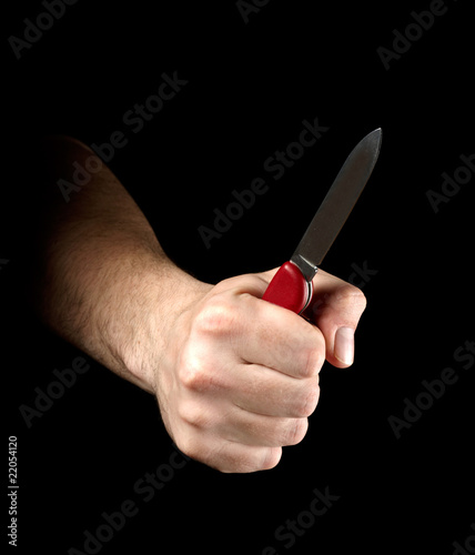 Knife in hand isolated on black background
