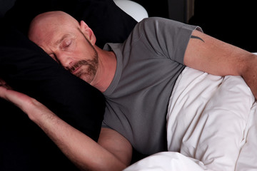 Bald middle aged man sleeping