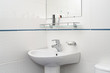 White bathroom with mirror and washbowl faucet and tooth brushes