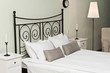 Forged headboard of bed with pillows and white coverlet
