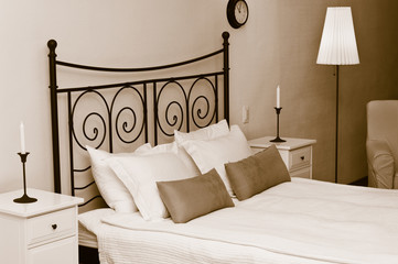 The forged headboard of bed with pillows and white coverlet