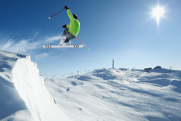 Jumping Skier in alpine mountains