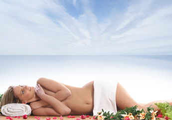 A young woman is getting spa treatment on a resort background
