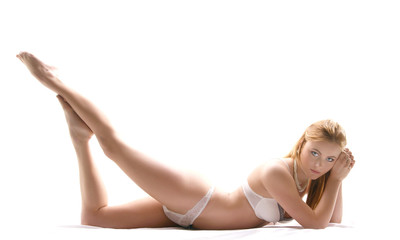 A young and attractive redhead girl is lying in erotic lingerie