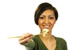 Young woman holds a piece of cauliflower with chopsticks.