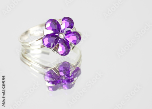 Pretty purple costume jewelry ring on mirrored surface