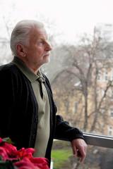 Senior steht einsam, deprimiert, traurig bei Fenster