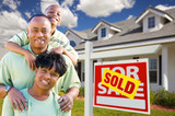 African American Family with Sold For Sale Sign and House