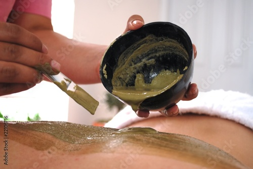 woman in spa with mud on her back