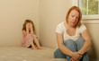 Mom and daughter sitting on an old mattress looking concerned